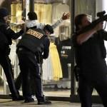 2日、ウィーン中心部で、身体検査を行う警官たちと、上方からの銃撃を警戒する警官(AFP時事)