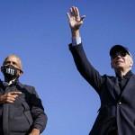 31日、米中西部ミシガン州フリントの選挙集会で、声援に応えるオバマ前大統領(左)とバイデン前副大統領(AFP時事)