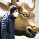 株価上昇を象徴する米ウォール街のチャージング・ブル像の前を新型コロナ感染拡大後にマスク姿で歩く人(UPI)