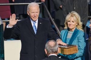 20日、米ワシントンの連邦議会議事堂前の就任式で宣誓するバイデン新大統領(左)とそばに立つジル夫人(AFP時事)
