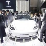中国・北京で開かれたモーターショーに展示された米テスラ社の電気自動車を見る人々(UPI)