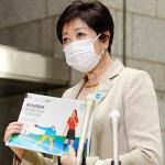 東京五輪・パラリンピックの感染症対策をまとめた「プレーブック」を手に取材に応じる小池百合子東京都知事=10日夜、都庁