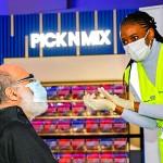 10日、英南東部メードストンで、新型コロナウイルスのワクチン接種に臨む男性(左)(AFP時事)