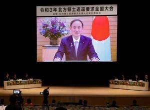 無観客で行われた北方領土返還要求全国大会で、ビデメッセージであいさつする菅義偉首相(画面内)=7日午前、東京都渋谷区