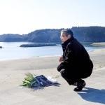 妻が見つかった小泉海岸で花と著書を手向ける佐藤誠悦さん=11日午前8時頃、宮城県気仙沼市本吉町