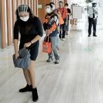 マニラ首都圏の商業ビルでフェイスシールドを着用し入場制限のために並ぶ人々(1月撮影)