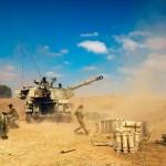13日、イスラエル・スデロット近郊の拠点からガザ地区に向けて砲撃するイスラエル兵(AFP時事)