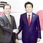 会談前、韓国の文在寅大統領(左)と握手する安倍晋三首相(当時)