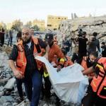 13日、パレスチナ自治区ガザ北部で、イスラエル軍の空爆で崩壊した住居で発見された犠牲者の遺体を運ぶ救助隊(AFP時事)