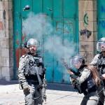 14日、ヨルダン川西岸のパレスチナ自治区ヘブロンで、デモ隊に催涙弾を発射するイスラエル治安部隊(AFP時事)