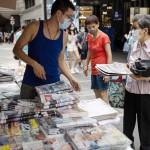 18日、香港の新聞スタンドで「リンゴ日報」を買い求める女性(EPA時事)