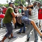 11日、キューバの首都ハバナで、反政府デモの最中に拘束される男性(中央)(AFP時事)