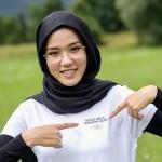 五輪のロゴ入りTシャツを着てポーズを取るアフガニスタン出身のメーソマ・アリザダ選手=1日、スイス・エーグル(AFP時事)