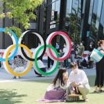 開会式を翌日に控え、国立競技場近くの五輪モニュメント前で記念撮影をする人たち=22日、東京都新宿区