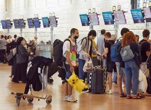 イスラエルのベングリオン国際空港でチェックインのために並ぶ人々=6月23日、UPI