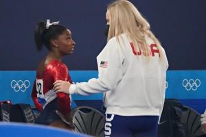 東京オリンピックの体操女子団体決勝戦の途中棄権を決めた米国のシモーネ・バイルズ選手(写真左・UPI)