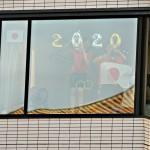 国立競技場の前にあるビルから日の丸を掲げて応援する人=23日、都内