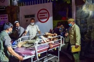 6日、カブールの空港周辺の爆発で、負傷した男性を搬送する医療関係者(AFP時事)