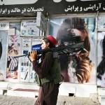 スプレーで黒く塗られた女性の顔のポスターと、アフガンのイスラム主義組織タリバンの戦闘員=18日、カブール(AFP時事)