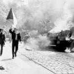燃えるソ連の戦車と国旗を掲げるチェコスロバキアの人々(Wikipediaより)