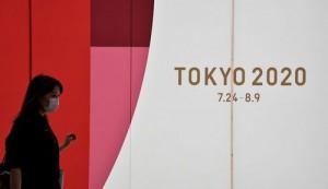 東京五輪のボード前を歩く歩行者(UPI)