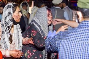 26日、カブール空港周辺の爆発で負傷し治療を求めて病院に着いた女性(AFP時事)