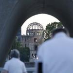 被爆76年目を迎える朝、平和記念公園の原爆死没者慰霊碑を訪れ祈りをささげる人たち=6日午前、広島市中区