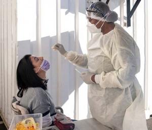 新型コロナウイルスの検査を受ける女性(左)=6月28日、南アフリカ・ヨハネスブルク(AFP時事)