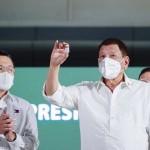 新型コロナウイルスワクチンの瓶を持つフィリピンのシャヒーン氏 ドゥテルテ大統領=3月4日、マニラ(AFP時事)