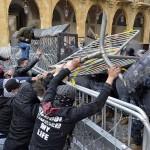 18日、ベイルートで、金属製の防護柵で警官隊を襲うデモ隊(EPA時事)