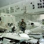 世界貿易センター1の建物の前の瓦礫の中を歩く消防士(ニューヨーク2001年9月11日 UPI)