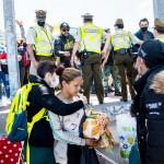 25日、チリ北部イキケで、デモ隊に襲われそうになったベネズエラ不法移民(手前)を守るチリ警察(AFP時事)