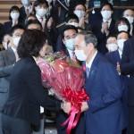職員から花束を手渡される菅義偉首相(手前右)=4日午後、東京・永田町