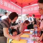 7月1日、香港島湾仔(ワンチャイ)の中国返還17周年の祝賀イベントでセントラル占拠計画に反対する署名をする親中派の人々