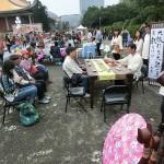台湾の民謡を太鼓でたたきながら歌う女性の声を聞きながら台湾茶を一服する人たち (2)