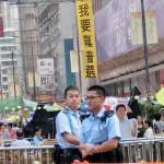 デモ現場を見守る香港の警官ら