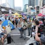 占拠デモ現場で香港有線テレビの取材を受ける香港の若手歌手・黎曉陽さん(左)