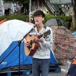 金鍾(アドミラルティー)の占拠デモ現場で雨傘革命についての曲をギター弾き語りで歌う若手歌手・黎曉陽さん(左)